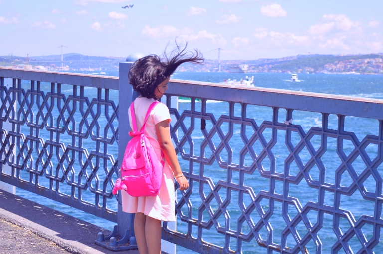 Little girl on the Galata Bridge in the city of Istanbul looking photography